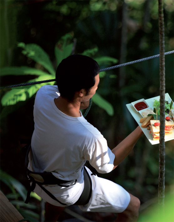 A zip-lining waiter enroute to the Soneva Kiri Treetop Dining Pod
